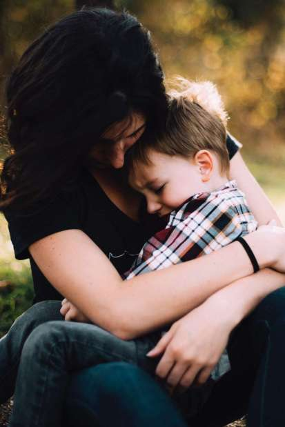 A mom hugging her upset son.